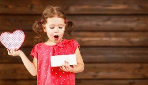 Little girl opening Valentine's Day gift from Pelham dentist for kids