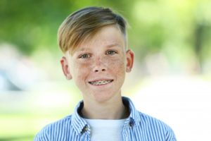Smiling young boy with orthodontic treatment outside