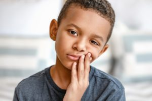 Young boy with toothache because of cavities