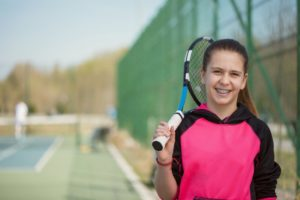 girl with tennis racket playing sports with braces
